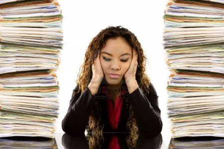 6635706-stock-image-of-woman-sitting-at-desk-with-a-pile-of-paperwork-on-each-side